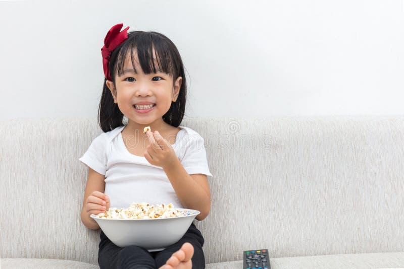 Szczęśliwy Azjatycki Chiński małej dziewczynki łasowania popkorn na kanapie obrazy royalty free