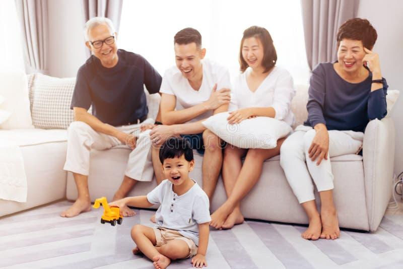 Szczęśliwy Azjatycki dalszej rodziny obsiadanie na kanapie i dopatrywania małym dziecku bawić się zabawkę na podłoga z szczęściem obrazy royalty free