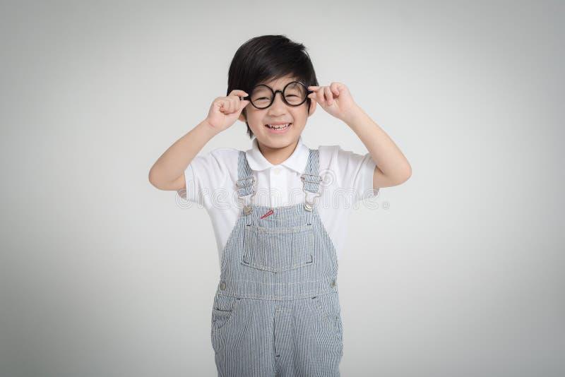 Szczęśliwy Azjatycki dziecko jest ubranym szkieł ono uśmiecha się obrazy stock