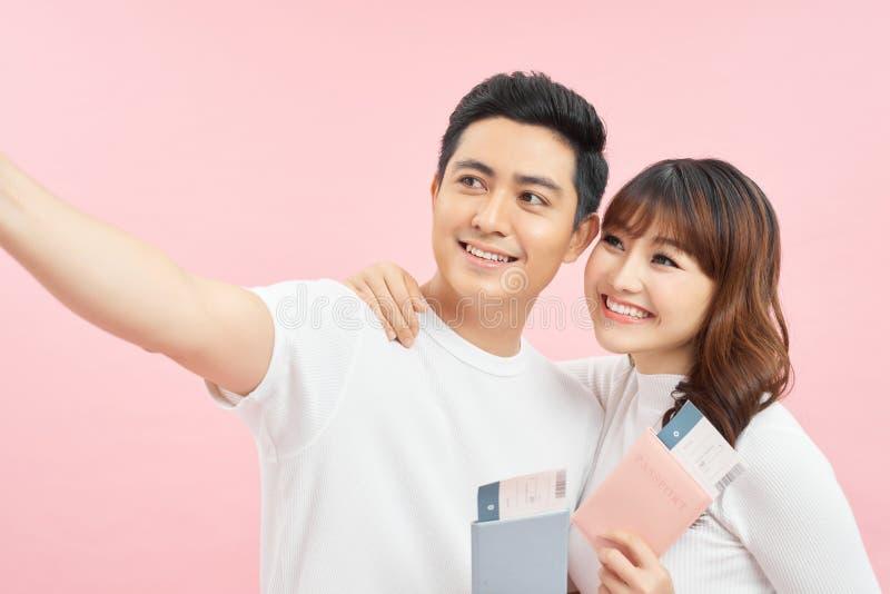 Szczęśliwy azjatycki mężczyzna i kobieta trzymający paszporty i bilety lotnicze patrząc na kamerę izolowaną na różowym zdjęcie royalty free