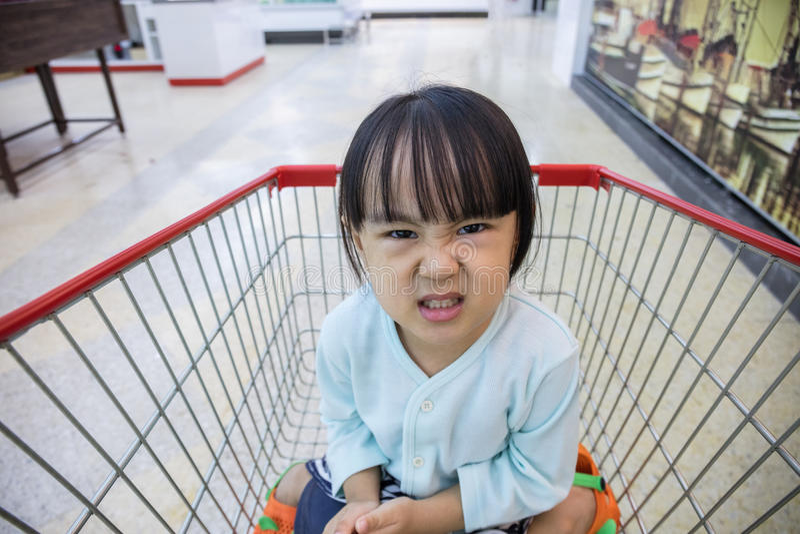 Szczęśliwy Azjatycki Mały Chiński dziewczyny obsiadanie w wózek na zakupy zdjęcia stock