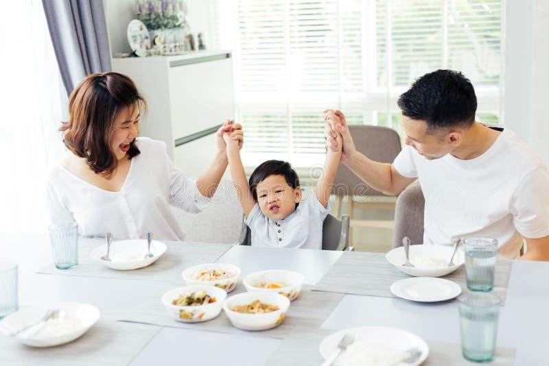 Szczęśliwy Azjatycki rodzinny dźwigania dziecka ` s wręcza up i uśmiechniętego podczas gdy mieć posiłek wpólnie zdjęcia stock