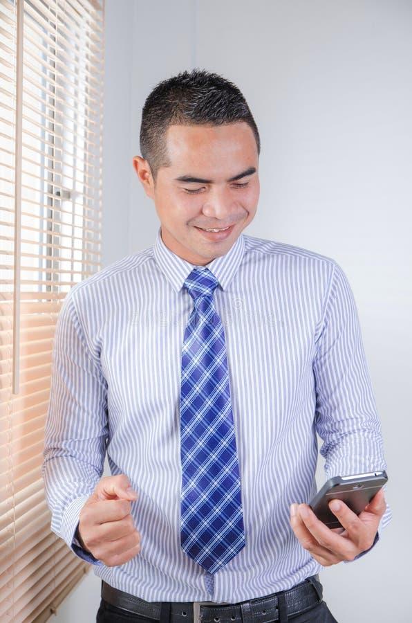 Szczęśliwy azjatykci biznesowy mężczyzna patrzeje mądrze telefon z szczęściem a zdjęcia stock