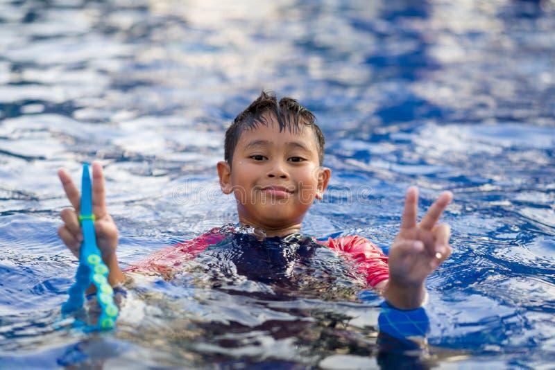 Szczęśliwy azjatykci dzieciak chłopiec dopłynięcie na basenie w lecie zdjęcie stock