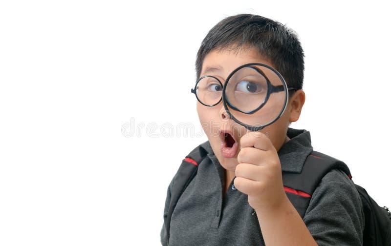 Szczęśliwy azjatykci gruby chłopiec mienia powiększać - szkło obrazy stock
