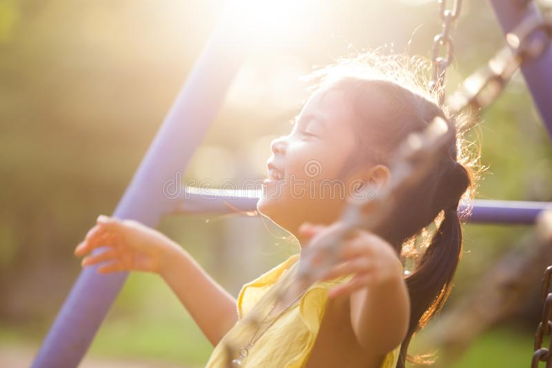 Szczęśliwy azjatykci małe dziecko dziewczyny latanie na huśtawce w boisku obraz stock