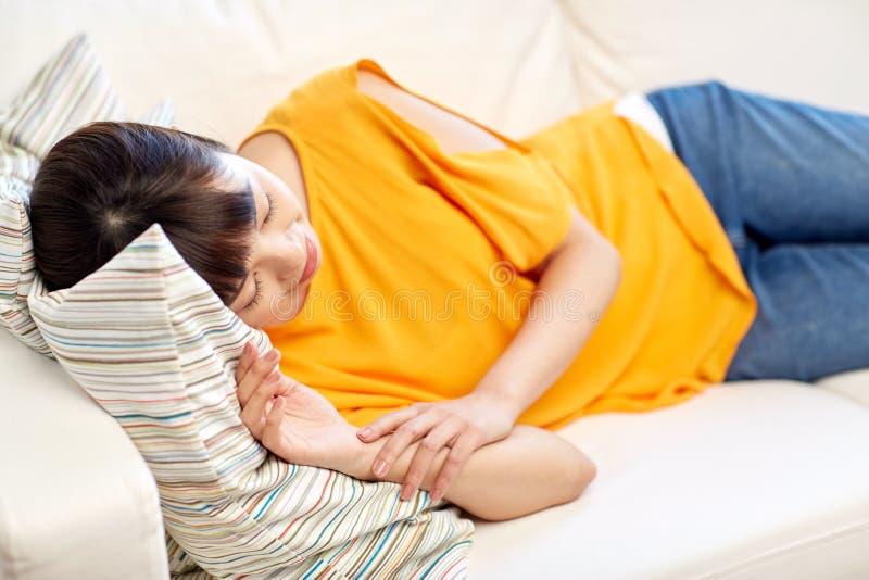 Szczęśliwy azjatykci nastoletniej dziewczyny dosypianie na kanapie w domu obrazy royalty free