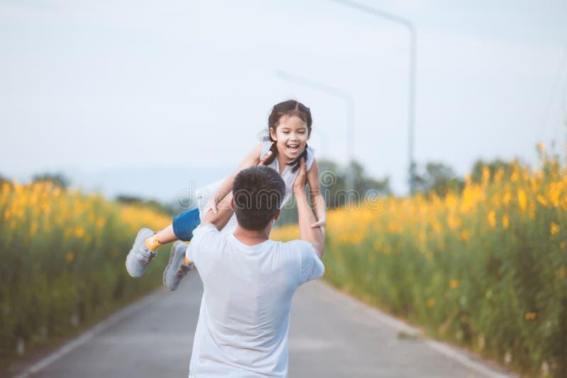 Szczęśliwy azjatykci ojciec trzyma jego przędzalniany z zabawą wokoło dzieciak fotografia stock