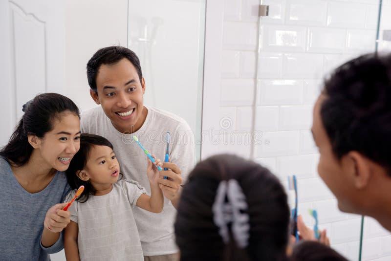 Szczęśliwy azjatykci rodziny muśnięcie ich zęby wpólnie zdjęcie stock