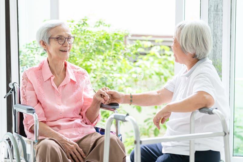 Szczęśliwy azjatykci starszy kobiety obsiadanie na wózku inwalidzkim, siostrze lub przyjacielu z piechurem ma zabawę, życzliwi, ż obraz royalty free
