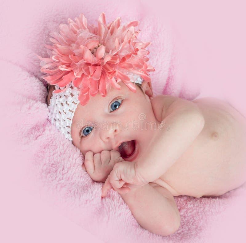 Szczęśliwy błękit przyglądająca się dziewczynka z kwiatem i kapitałką fotografia royalty free
