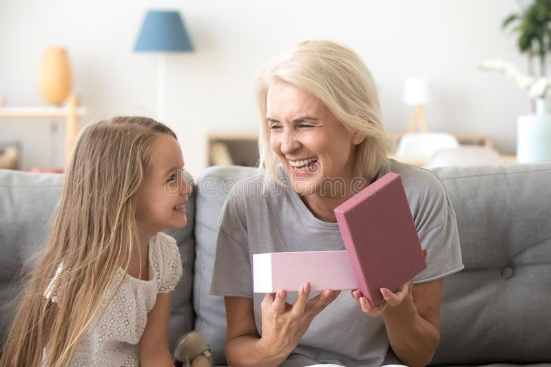 Szczęśliwy babci otwarcia prezenta pudełko z teraźniejszością od wnuka zdjęcia royalty free