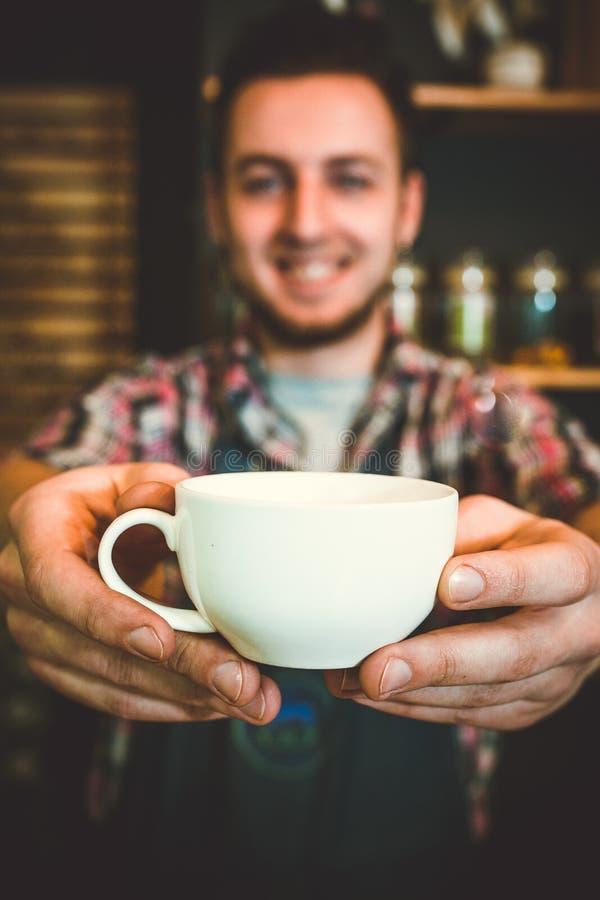 Szczęśliwy barista oferuje filiżankę kawy kamera zdjęcie stock