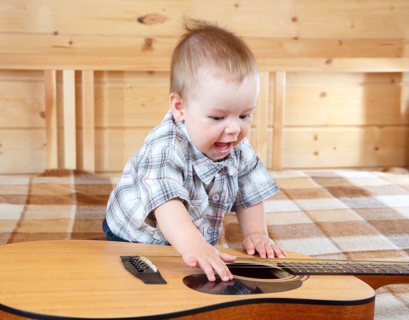 Szczęśliwy berbeć bawić się gitarę zdjęcie stock