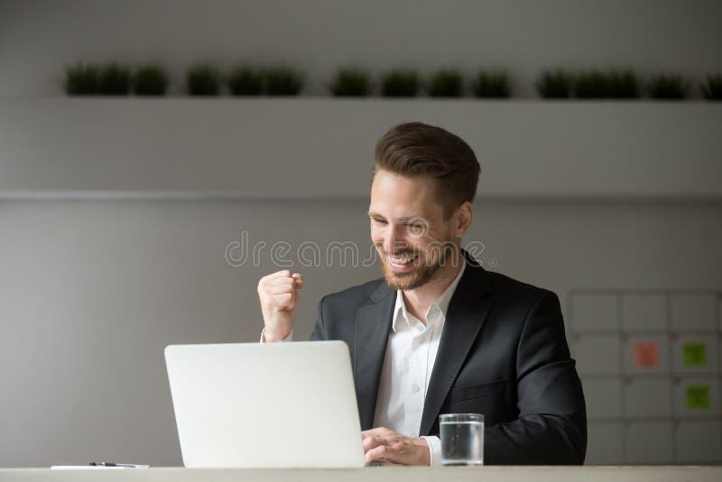 Szczęśliwy biznesmen świętuje biznesowego sukcesu wygrany online lookin zdjęcie stock