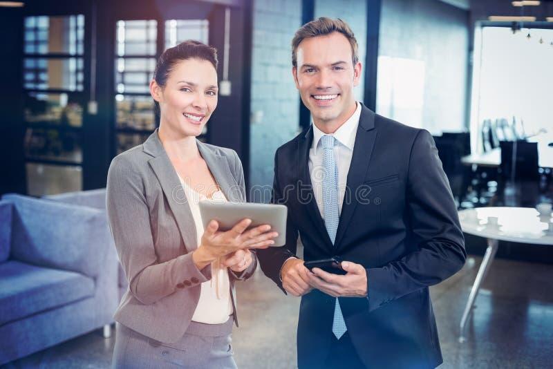 Szczęśliwy biznesmen i bizneswoman z cyfrową pastylką i telefonem komórkowym obrazy royalty free
