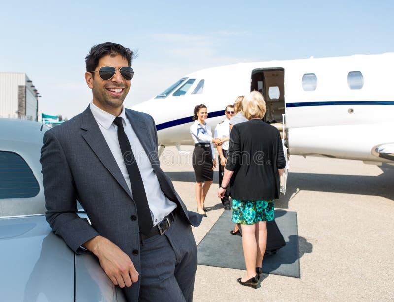 Szczęśliwy biznesmen Opiera Na samochodzie Przy lotniskiem fotografia stock