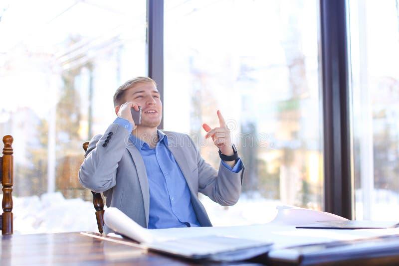 Szczęśliwy biznesmen opowiada smartphone o szkicu projekcie przy c zdjęcia stock