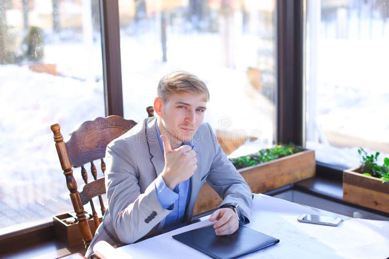 Szczęśliwy biznesmen opowiada smartphone o szkicu projekcie przy c obraz stock