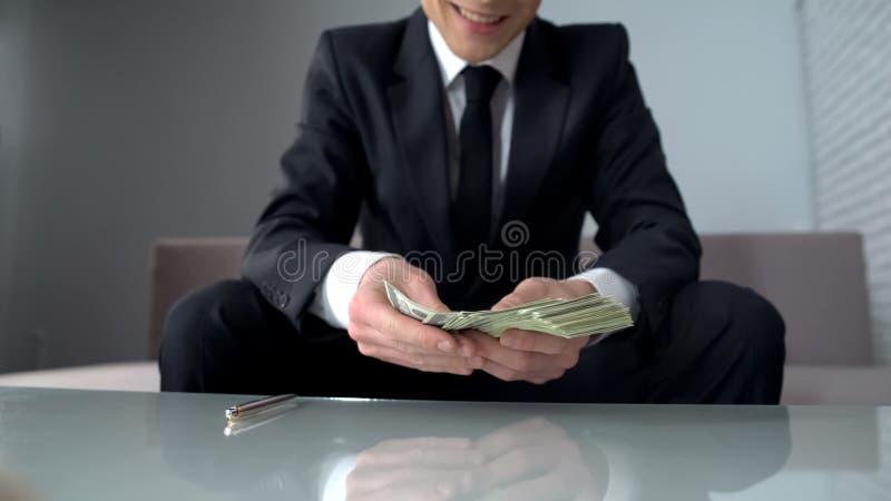 Szczęśliwy biznesmen otrzymywa dużą pożyczkę od banka i ono uśmiecha się, pomyślny rozpoczęcie fotografia royalty free