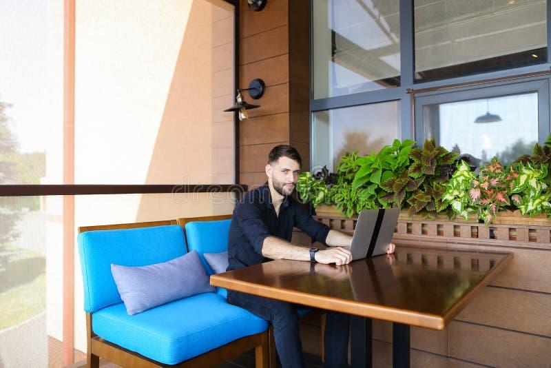 Szczęśliwy biznesmen patrzeje kamerę pracuje z laptopem i rozmową zdjęcia stock