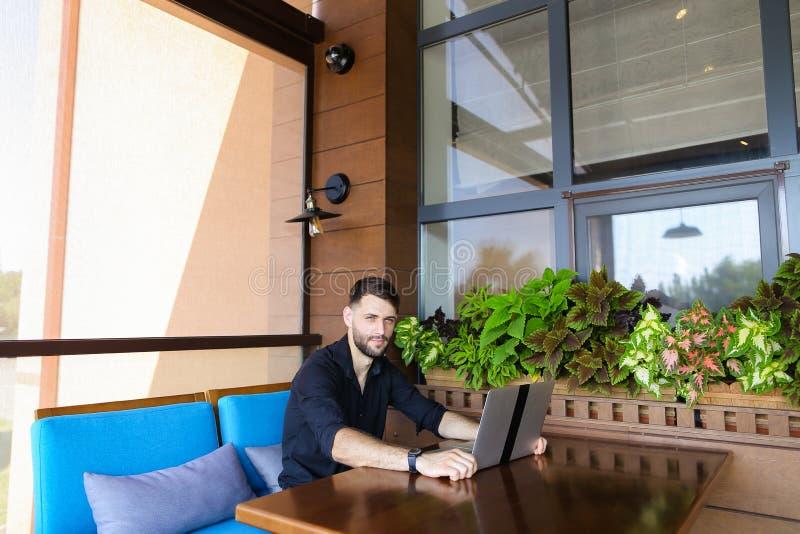 Szczęśliwy biznesmen patrzeje kamerę pracuje z laptopem i rozmową zdjęcie royalty free