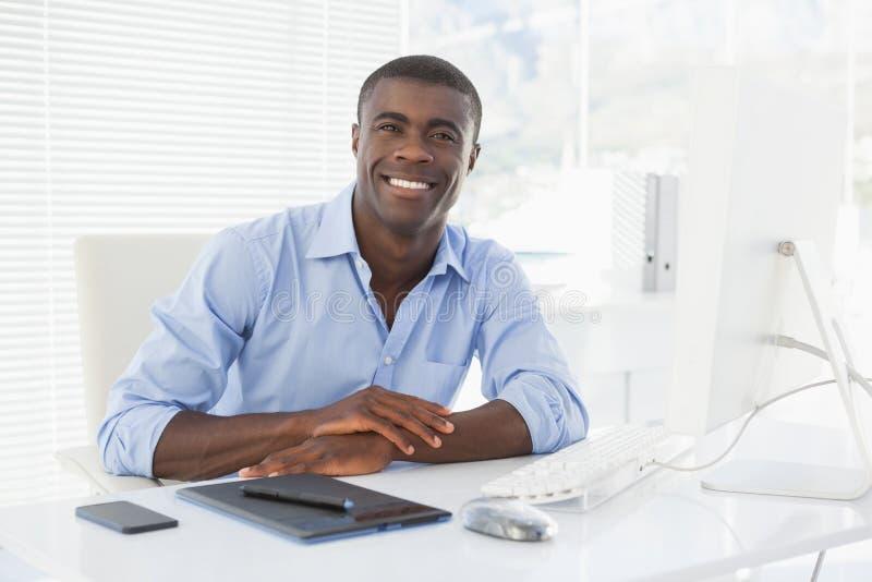 Szczęśliwy biznesmen pracuje przy jego biurkiem zdjęcie royalty free