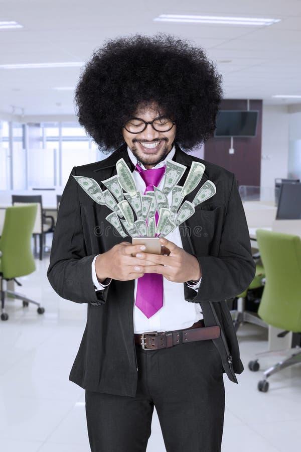 Szczęśliwy biznesmen robi pieniądze nad jego mądrze telefonem fotografia stock