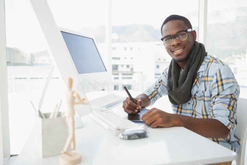 Szczęśliwy biznesmen używa digitizer przy biurkiem obrazy royalty free