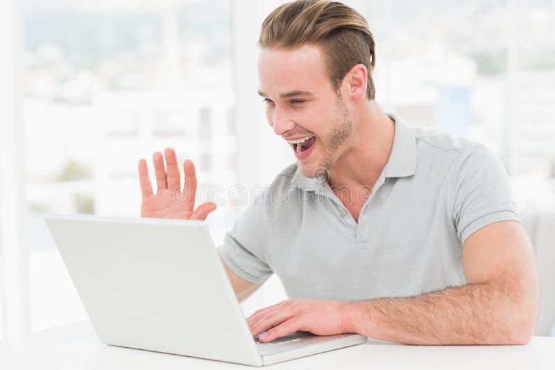 Szczęśliwy biznesmen używa laptop i gestykulować zdjęcie stock