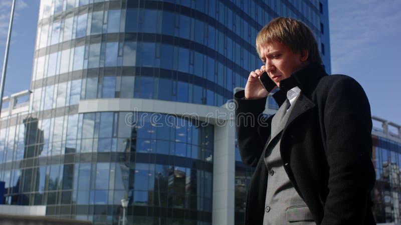 Szczęśliwy biznesmen używa telefon komórkowego na zewnątrz biura obraz royalty free