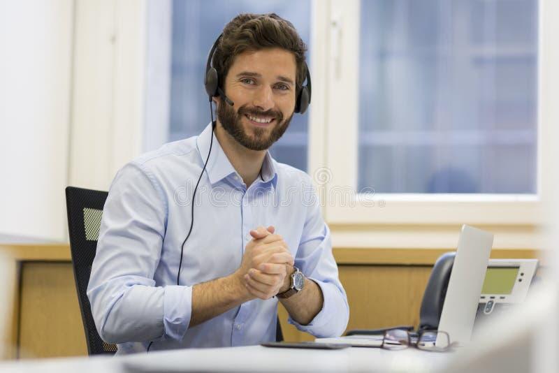 Szczęśliwy biznesmen w biurze na telefonie, słuchawki, Skype zdjęcie royalty free