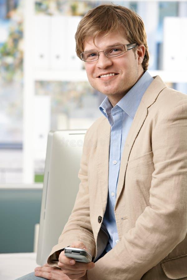Szczęśliwy biznesmen z telefonem komórkowym przy biurem fotografia royalty free
