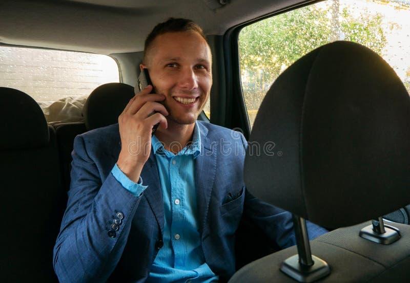 Szczęśliwy biznesmena obsiadanie w luksusowym samochodzie Młody brodaty mężczyzna jest ubranym garnitur używać jego smartphone zdjęcia stock