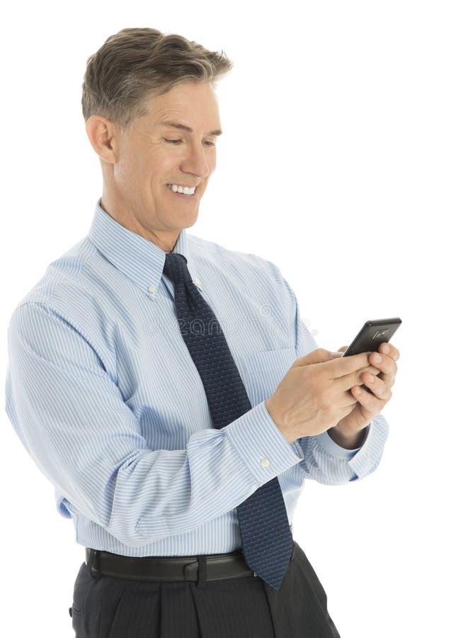 Szczęśliwy biznesmena wysylanie sms Przez Mądrze telefonu zdjęcie royalty free