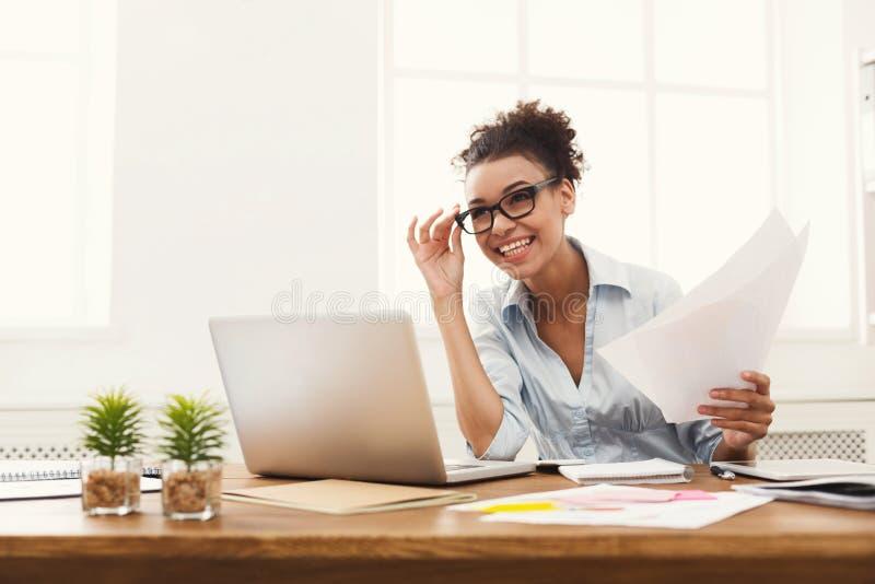 Szczęśliwy biznesowej kobiety czytania dokument przy biurowym desktop obrazy stock
