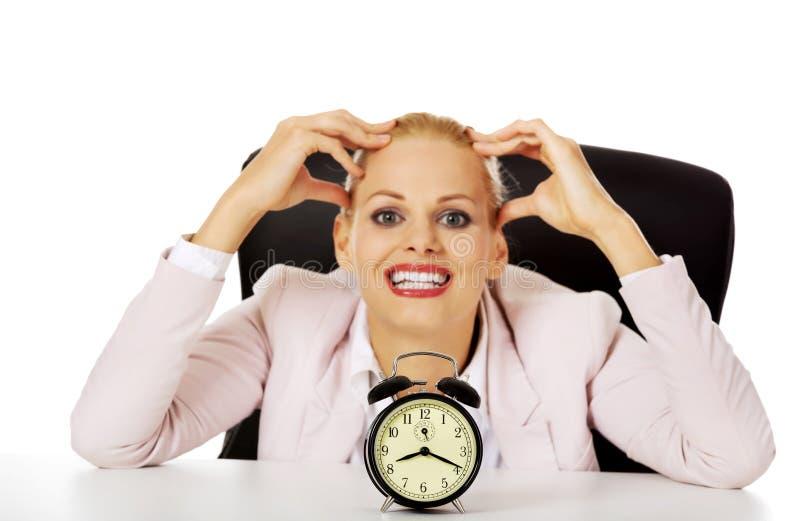 Szczęśliwy biznesowej kobiety obsiadanie za biurkiem z budzikiem zdjęcie stock