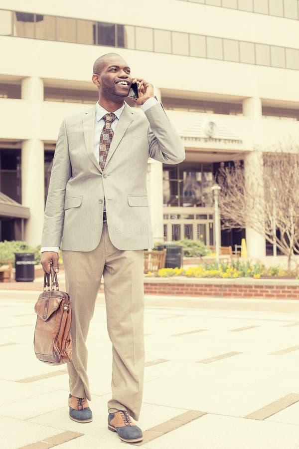 Szczęśliwy biznesowy mężczyzna opowiada na jego telefonie podczas gdy chodzący outside zdjęcia stock
