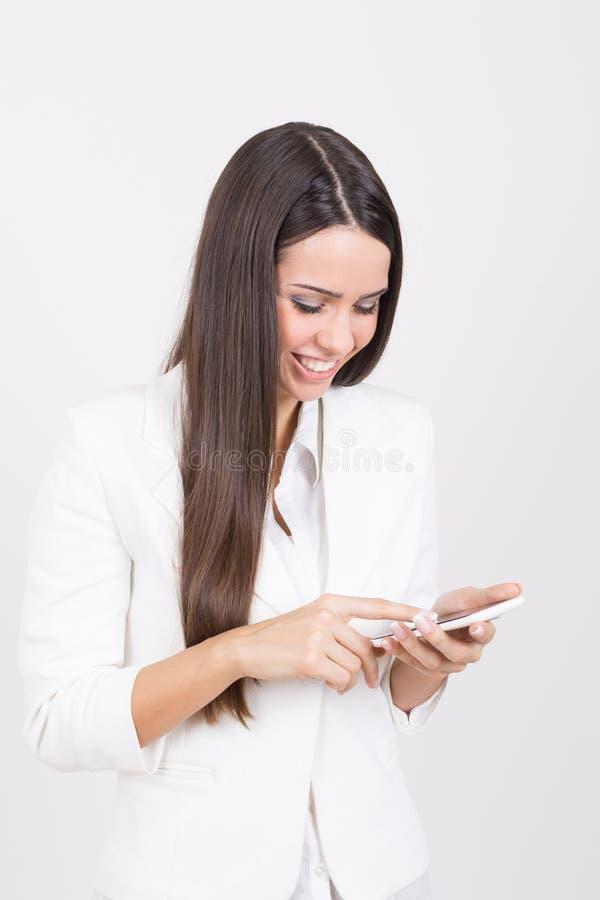 Szczęśliwy bizneswoman jest ubranym białego używa smartphone zdjęcia stock