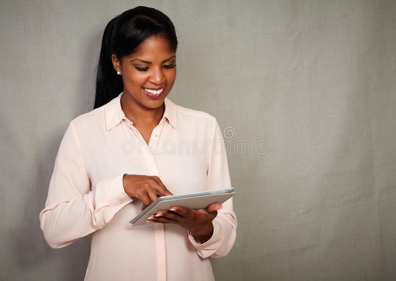 Szczęśliwy bizneswoman ono uśmiecha się podczas gdy używać pastylkę obrazy stock