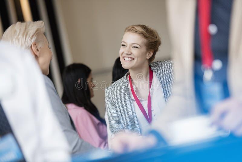 Szczęśliwy bizneswoman opowiada kolega przy lobby w convention center zdjęcia royalty free
