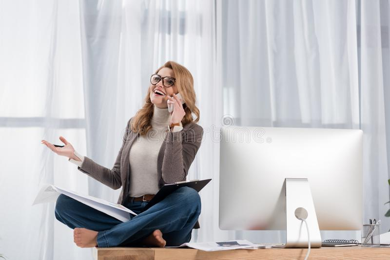 szczęśliwy bizneswoman opowiada na smartphone z papierami podczas gdy siedzący na stole obraz royalty free