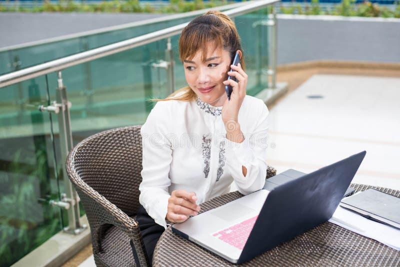 Szczęśliwy bizneswoman opowiada na telefonie komórkowym w biurze tele w domu obrazy stock