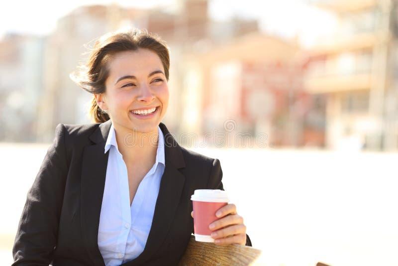 Szczęśliwy bizneswoman patrzeje daleko od przy kawową przerwą obraz royalty free