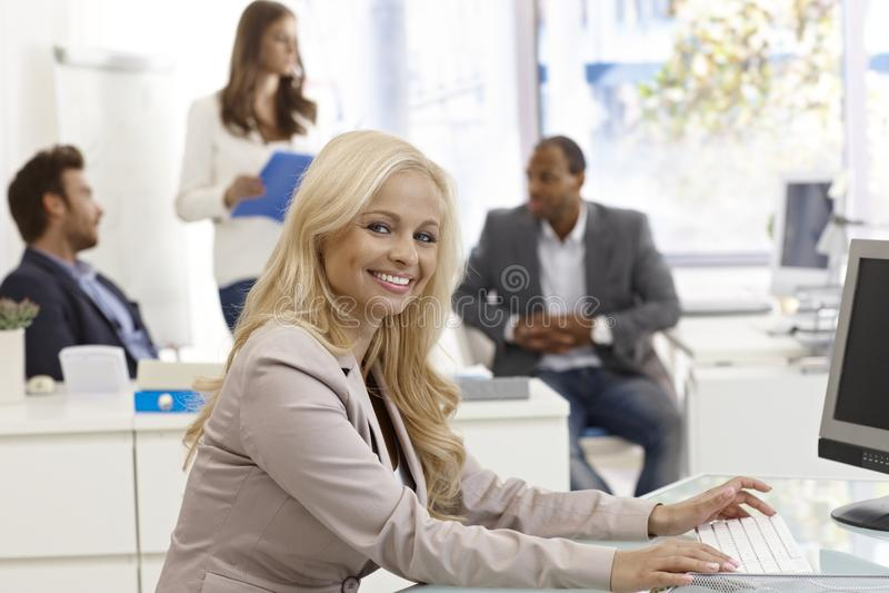 Szczęśliwy bizneswoman pracuje w ruchliwie biurze obraz royalty free