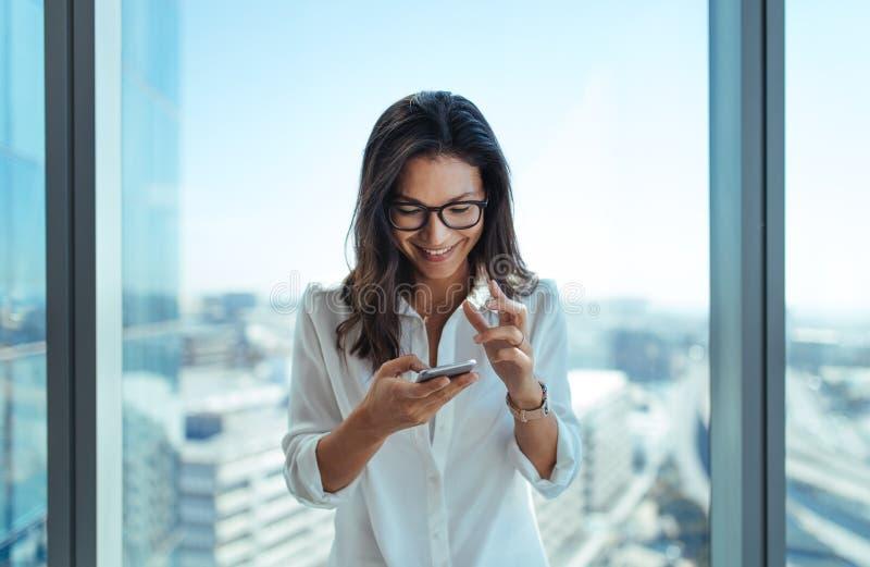 Szczęśliwy bizneswoman używa jej telefon komórkowego przy biurem obraz royalty free