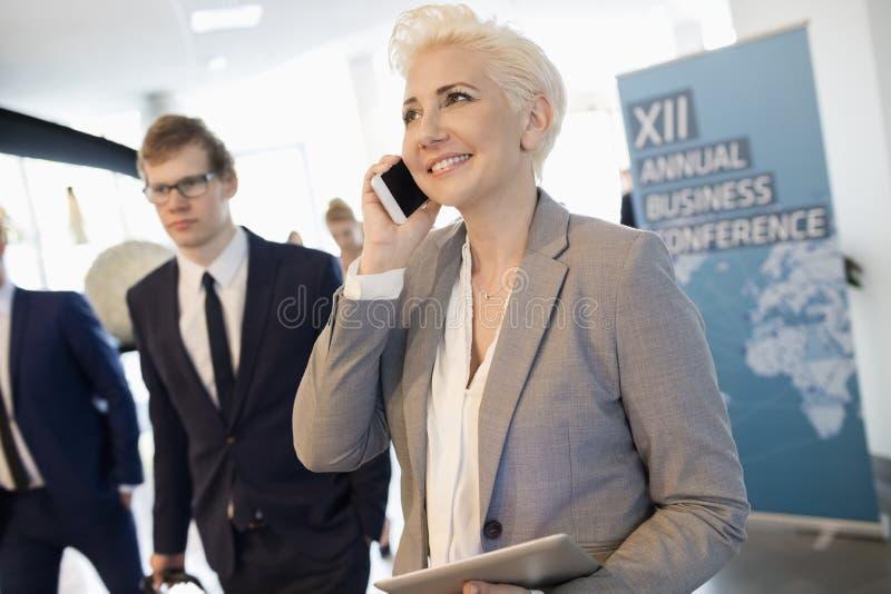 Szczęśliwy bizneswoman używa mądrze telefon przy convention center fotografia stock