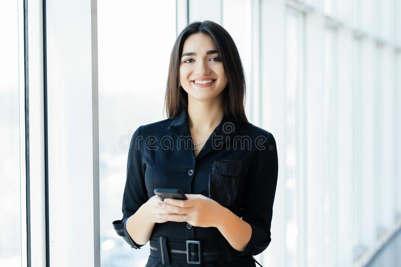 Szczęśliwy bizneswoman używa smartphone w biurowym pobliskim okno fotografia stock