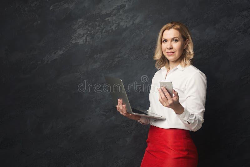 Szczęśliwy bizneswoman z laptopem i smartphone przy pracownianym tłem zdjęcie stock