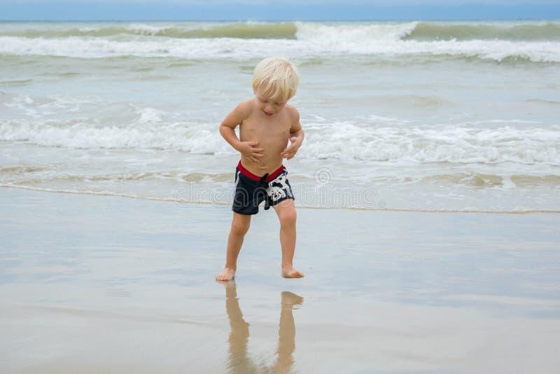 Szczęśliwy blond chłopiec dziecka odprowadzenie w wodzie przy dennego brzeg plażą, Nha Trang, Wietnam zdjęcia stock